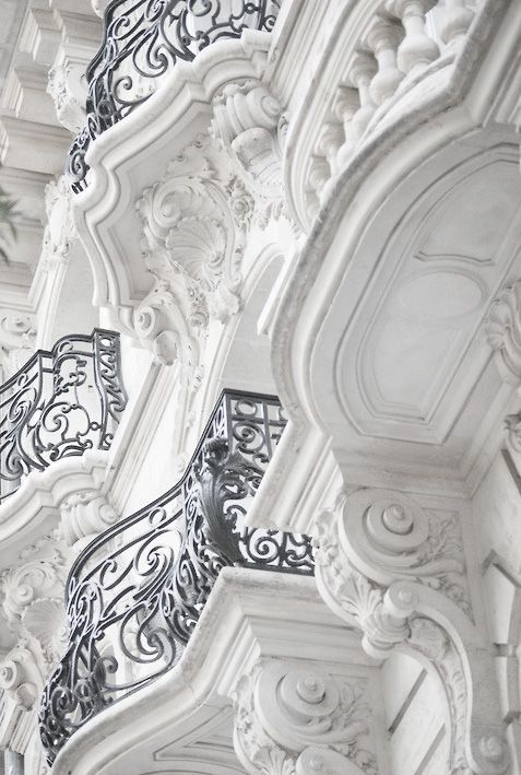 rows of ornate cast iron balconies on the side of a building in a french town